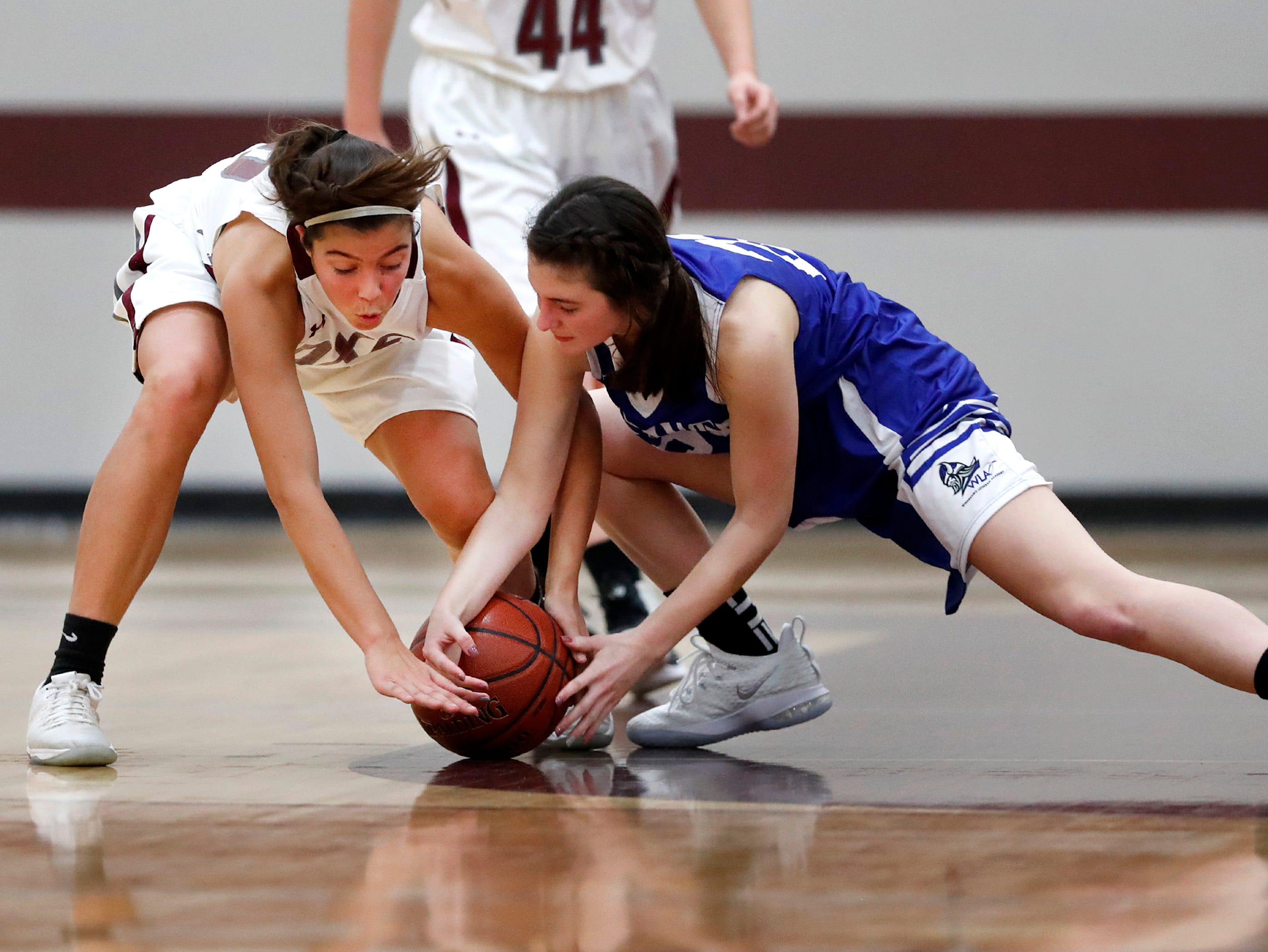 Fox Valley Lutheran High School's Maddie Jacobsen and Winnebago Lutheran Academy's Geneva Hewitt go after a loose ball Tuesday, Nov. 13, 2018, in Appleton, Wis. Fox Valley Lutheran High School lost to Winnebago Lutheran Academy 48-38.