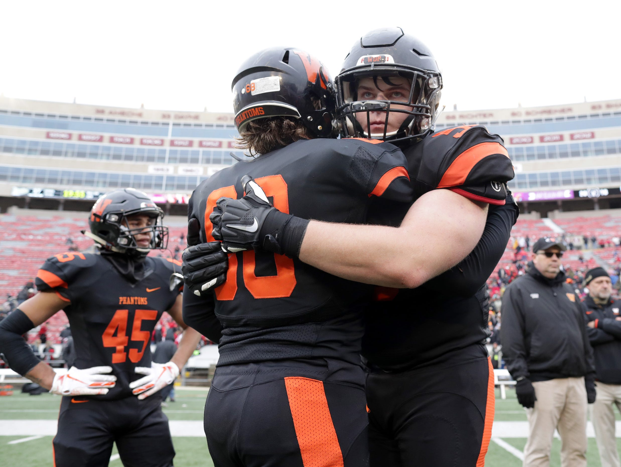 West De Pere High School's #68 Owyn Newman, left, and #58 Liam McDonough embrace after the Phantom's loss to Catholic Memorial High School during the WIAA Division 3 state championship football game on Friday, November 16, 2018, at Camp Randall in Madison, Wis.