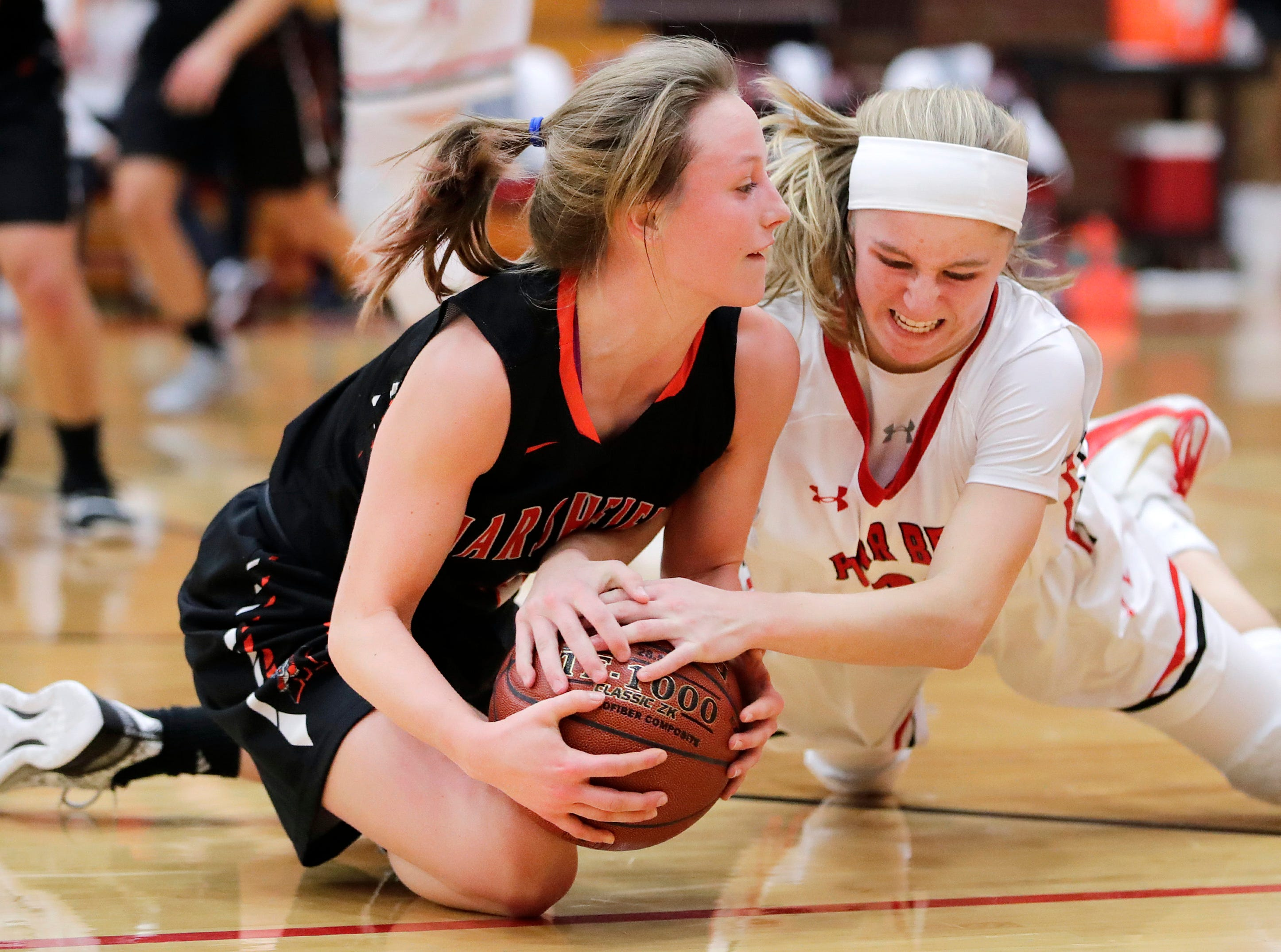 Marshfield High School's Kaydee Johnson and Hortonville High School's Kammy Peppler fight for control of a loose ball Thursday, Nov. 15, 2018, in Hortonville, Wis. Hortonville High School defeated Marshfield High School 59-47.