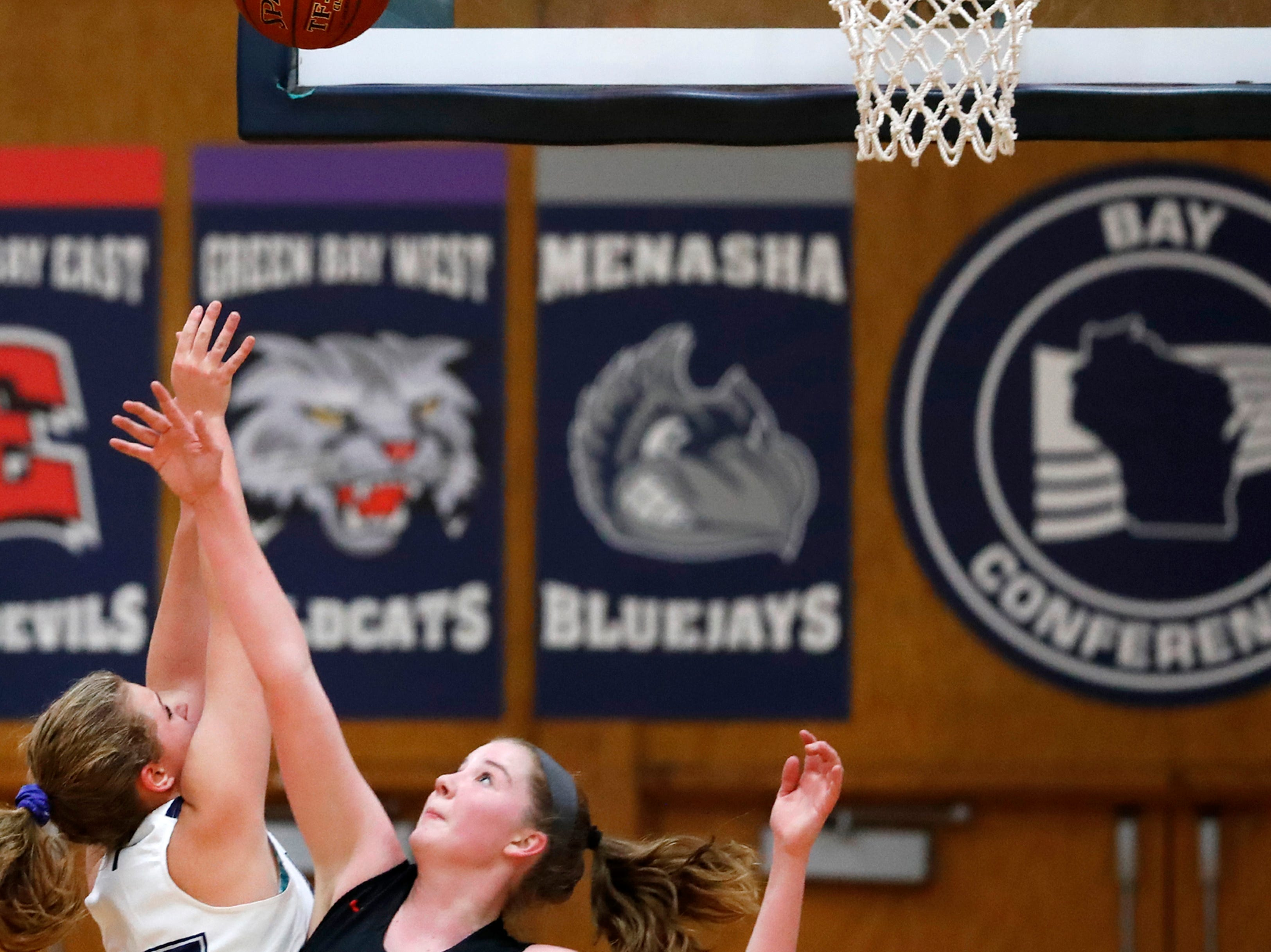 Xavier High School's Lauren Walkowski tries to get a shot past Lourdes Academy's Paige Droessler Wednesday, Nov. 14, 2018, in Appleton, Wis.
