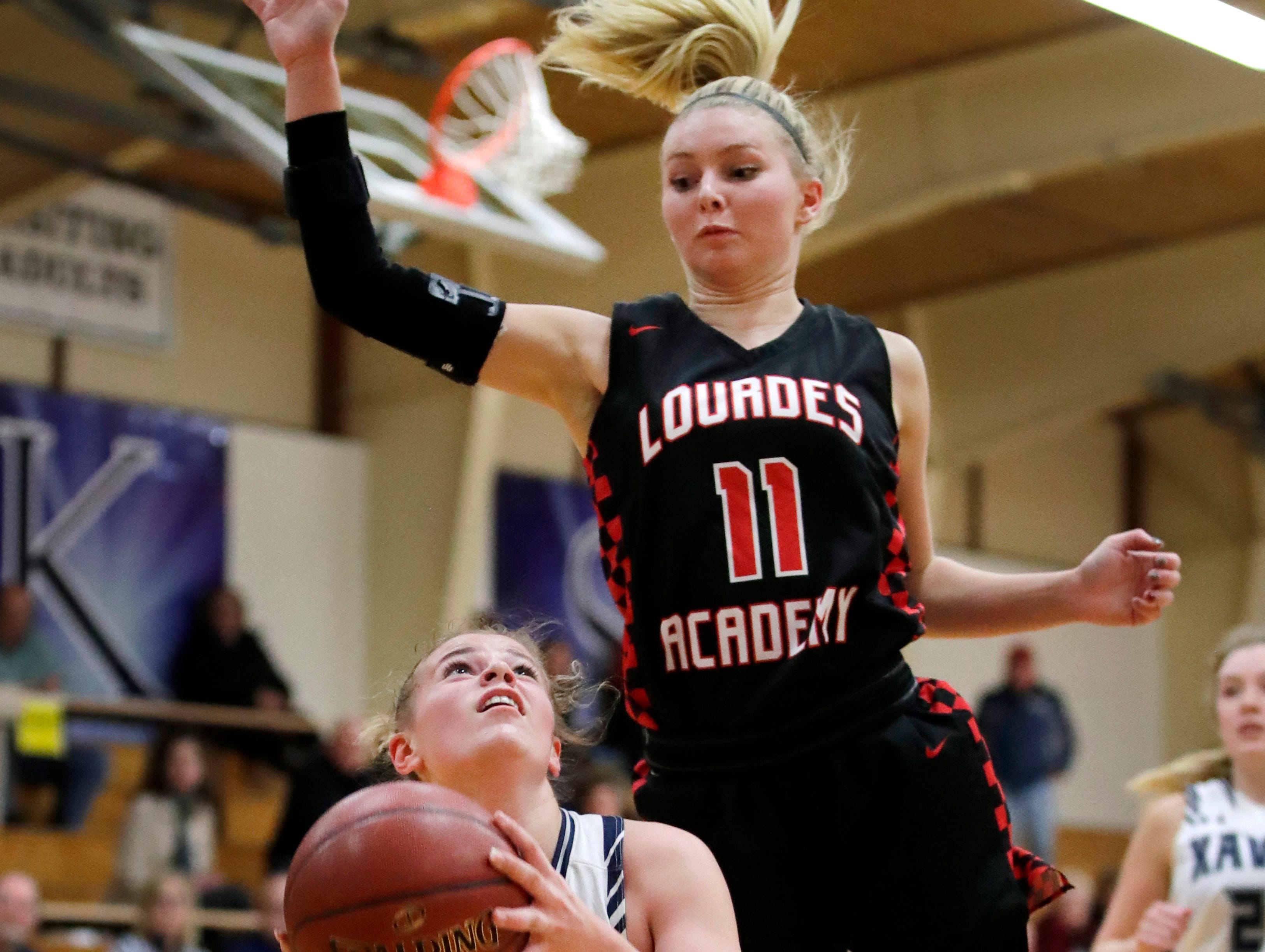 Xavier High School's Becca Feldkamp looks for a shot as Lourdes Academy's Alexis Rolph covers her Wednesday, Nov. 14, 2018, in Appleton, Wis. Xavier High School defeated Lourdes Academy 54-42.