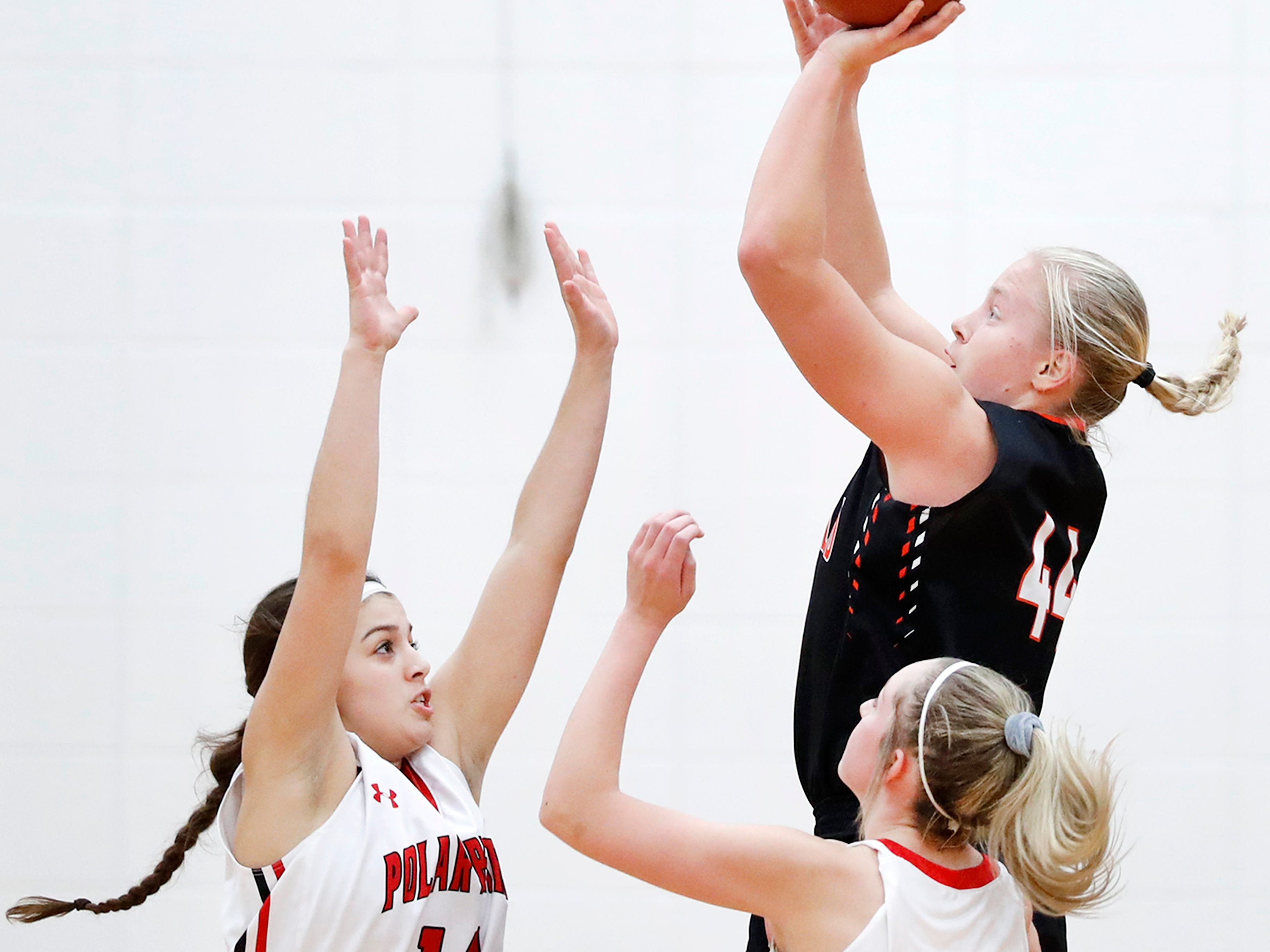 Hortonville High School's Tatum Hammen and Lexi Day try to cover Marshfield High School's Jenna Jakobi as she takes a shot Thursday, Nov. 15, 2018, in Hortonville, Wis.