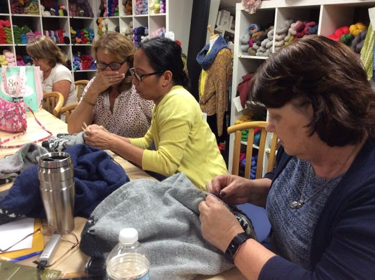 Patrons at Moore Yarn in Hazlet help each other with technique.