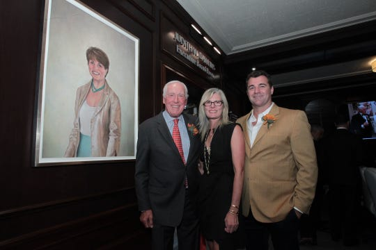 General Pete Dawkins, his daughter Noel and son-in-law Joe Mihalow with the portrait of Judi Dawkins that hangs in Monmouth Medical Center's board room named in Judi's honor.