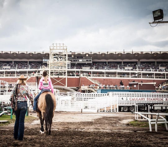Angela Ganter escorts her daughter, Jackie, to the arena for morning practice at the famous Calgary Stampede rodeo in Calgary, Alberta, in 2016.