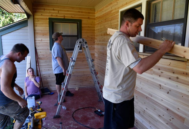 Desaree Elledge watches as Brandon Bartling (left), Bryan Travers and Jonathan Bilotta install siding on her porch Oct. 27. The men are part of Dyess Air Force Base's We Care Team; Elledge's late husband Justin was also a member. He died July 25 in a motorcycle accident in California.