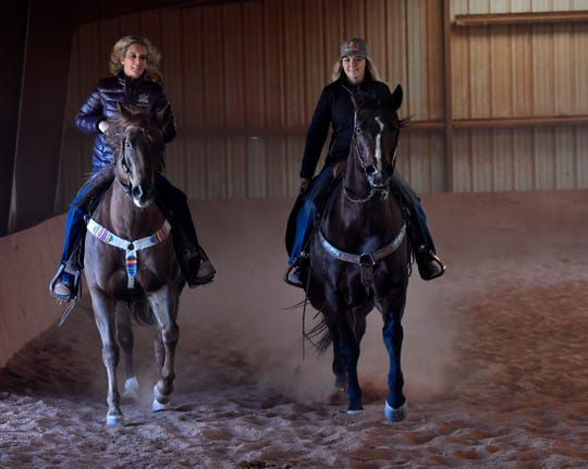 Angela Ganter and her daughter Jackie ride in their covered arena at Lone Star Stables on Nov. 19, 2018.