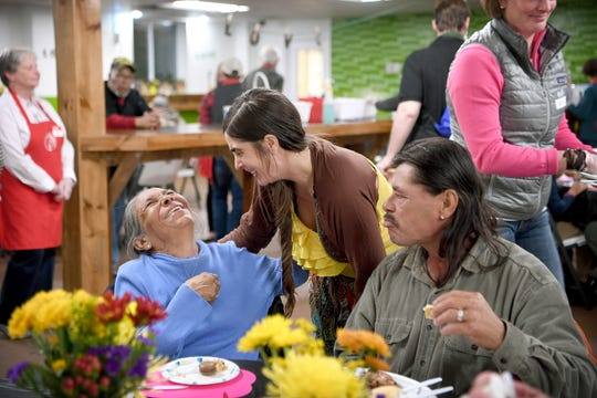 Gloria Glass, seated with her husband, James, laughs with Ajah Kapoutsos as they eat dinner at the Western Carolina Rescue Ministries during their second annual Week of Thankfulness on Nov. 19, 2018. Volunteers served dinner at WCRM every day of the week instead of just on Thanksgiving day.