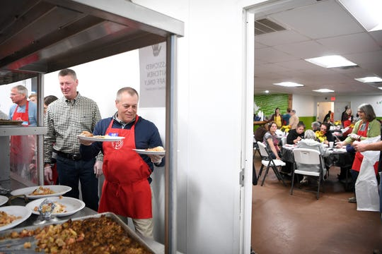 Hank Garbee walks to the dining room with plates of food as he volunteers at the Western Carolina Rescue Ministries during their second annual Week of Thankfulness on Nov. 19, 2018. Volunteers served dinner at WCRM every day of the week instead of just on Thanksgiving day.