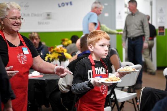 Lawson Edmonds, 10, serves plates of desserts as he volunteers at the Western Carolina Rescue Ministries during their second annual Week of Thankfulness on Nov. 19, 2018. Volunteers served dinner at WCRM every day of the week instead of just on Thanksgiving day.