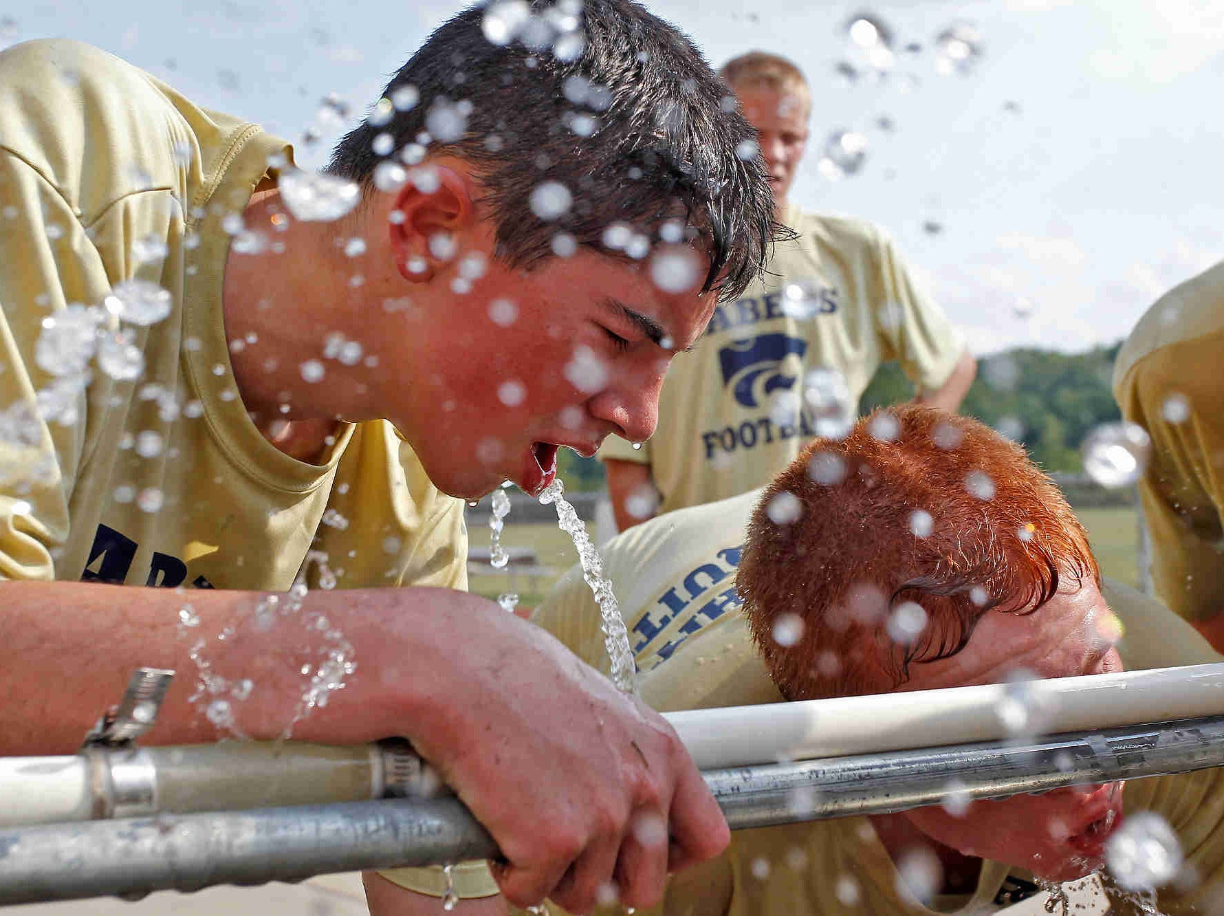 Players cool off Monday during football practice at Susquehanna Valley High School. It was the first day of high school practices in New York. First day of football practice at Susquehanna Valley High School. Monday, August 17, 2015.