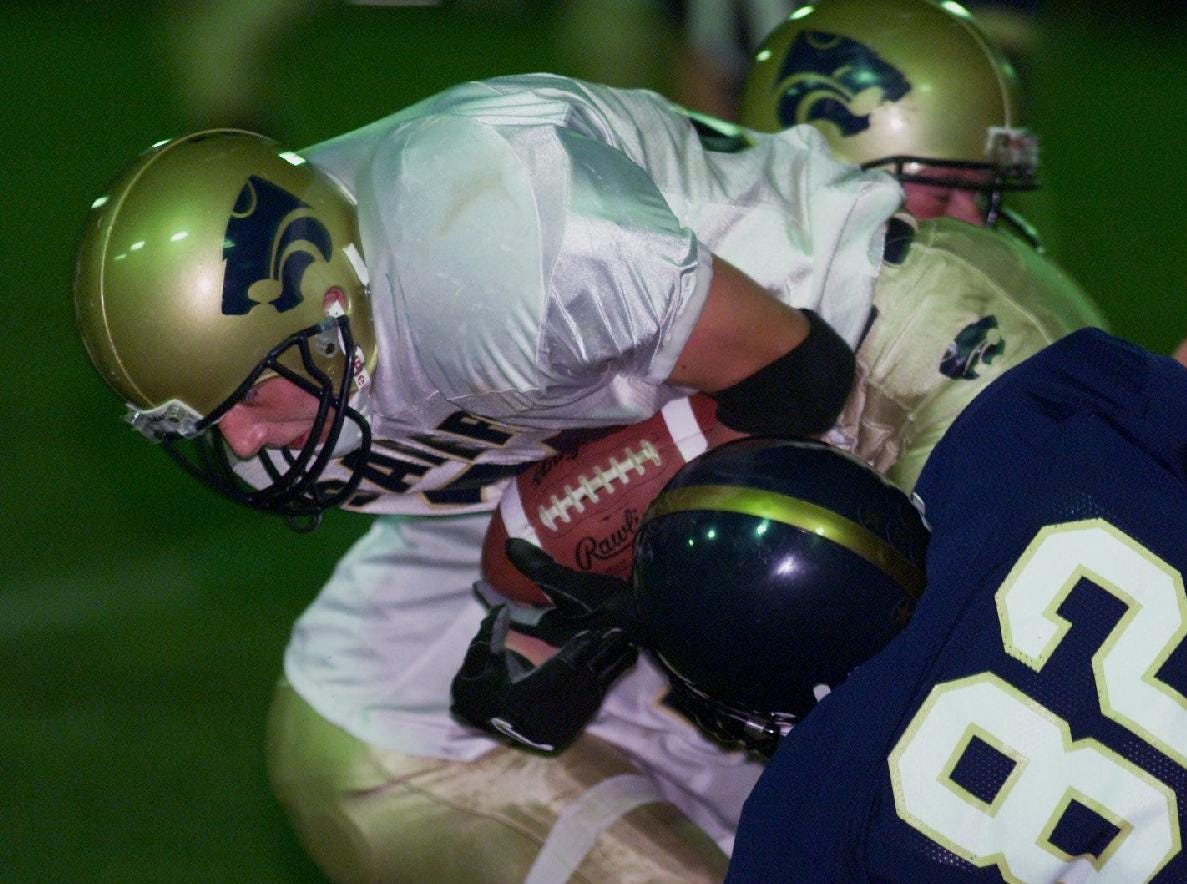 From 2001: SV Joshua Cronin braces for a tackle by Elmira Notre Dame Tom Huffner during Fri game in Elmira