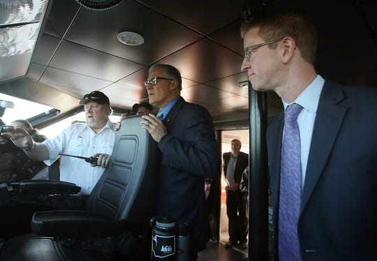 Kitsap Transit ferry Capt. Tom Healy (left) gives Governor Jay Inslee (center) and  U.S. Rep. Derek Kilmer a tour of the pilot house during the Grand Opening at the Port of Kingston for Kitsap Transit's new fast-ferry service between Kingston and Seattle on Monday, November 19, 2018.