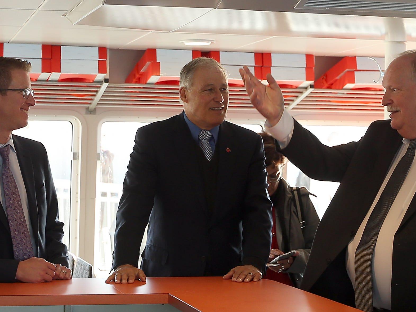 Kitsap Transit executive director John Clauson (right) talks with Jay Inslee (center) and  U.S. Rep. Derek Kilmer (left) aboard the M/V Finest on Monday, November 19, 2018.
