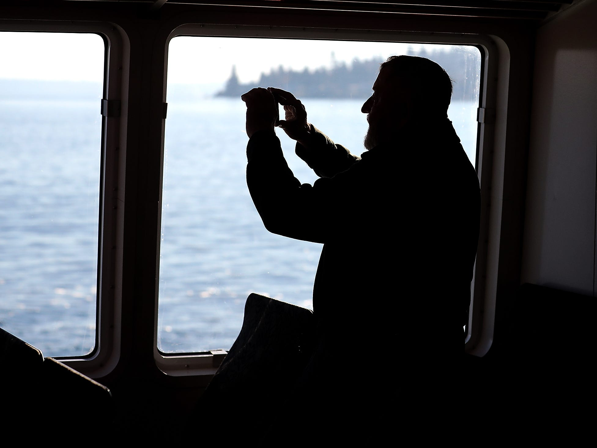 Peter Murphy, of Kingston, snaps photos out the window of the M/V Finest during the Grand Opening at the Port of Kingston for Kitsap Transit's new fast-ferry service between Kingston and Seattle on Monday, November 19, 2018.