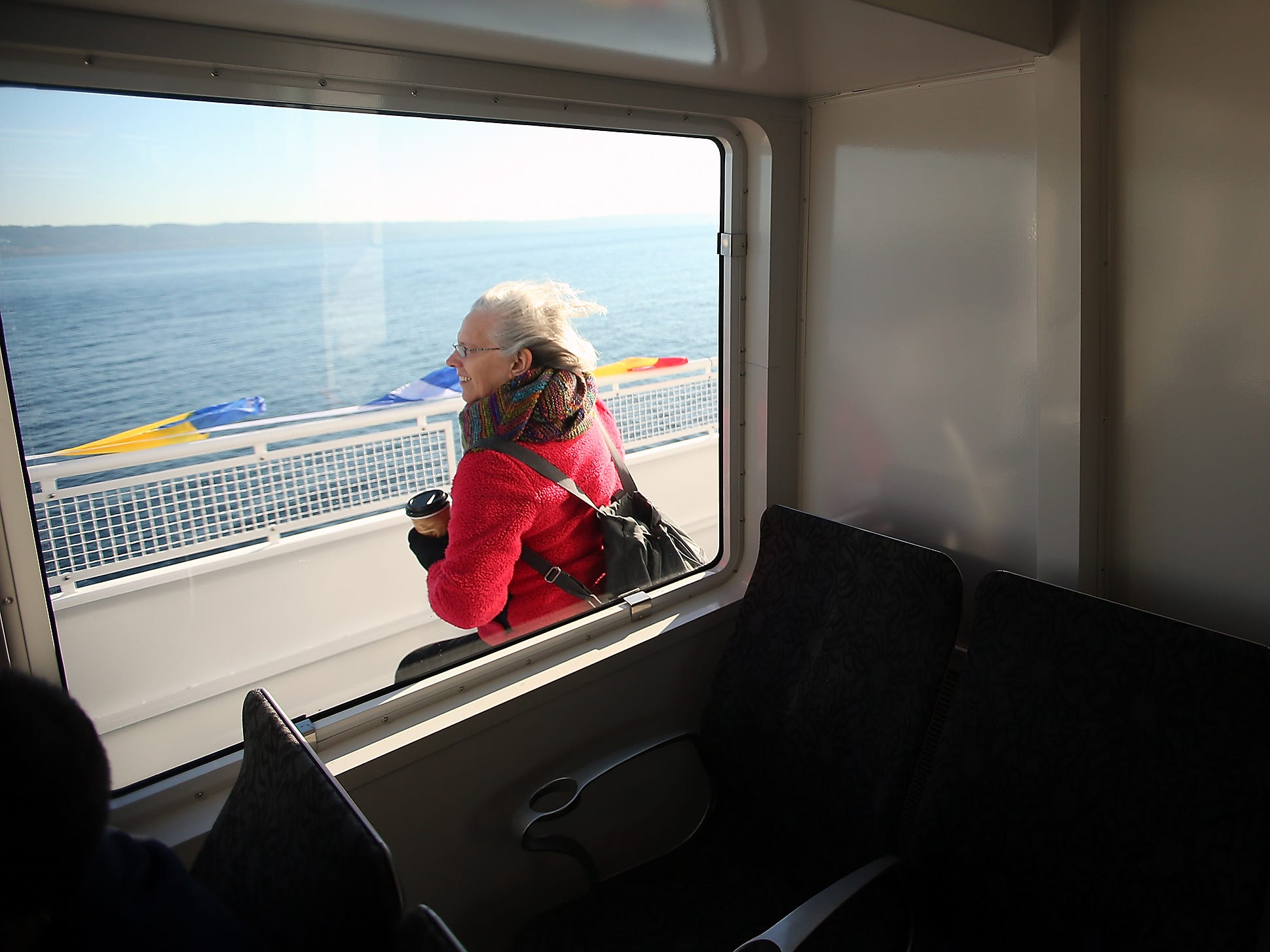 Maria Escobar, of Port Ludow, is framed by the cabin window as she braves the wind and the cold to sit outside during the grand opening ride of the M/V Finest on Monday, November 19, 2018.