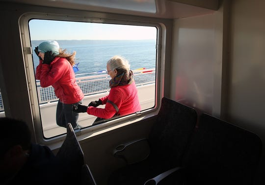 Shannan Yates (left) holds her hat down while fellow ferry rider Maria Escobar pulls on her gloves as the two brave the wind and cold to ride outside of the M/V Finest during the Grand Opening ride on Monday, November 19, 2018.