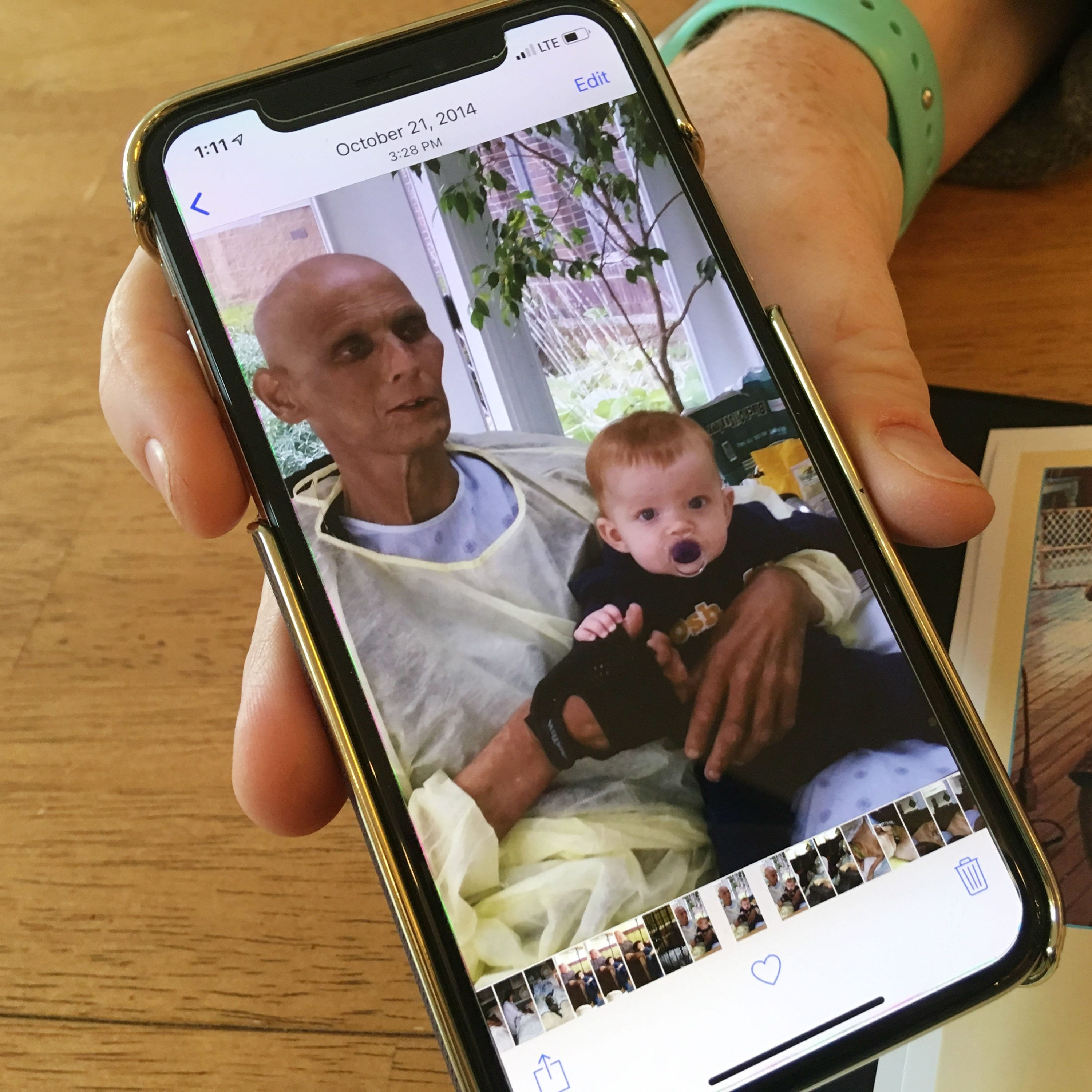 Janice Hutt shows a picture saved on her phone of her brother Bobby Hutt in the days before he died from cancer in October 2014 holding his lawyer's son