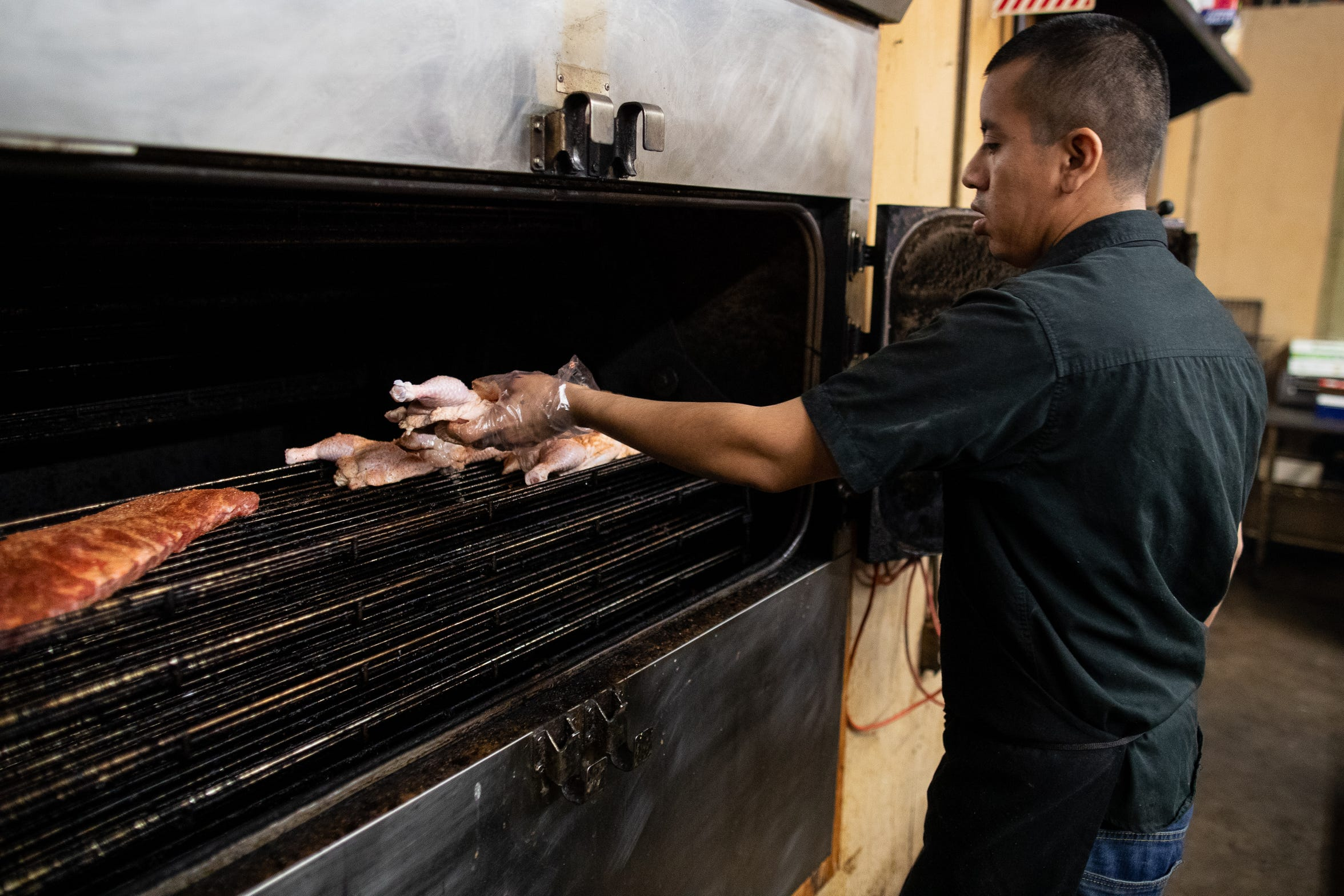 David Cabrera places chicken in the smoker at Bottomless Pit BBQ on Friday, Nov. 14, 2018.