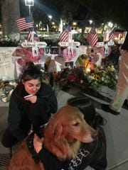 College students spend time with CeCe, an emotional support dog with Cherry Hill-based Tri-State K-9 Response Team at a vigil for victims of the Borderline bar shooting in Thousand Oaks, Calif. The team spent five days in California helping those affected by the Thousand Oaks bar shooting and wildfires in California.