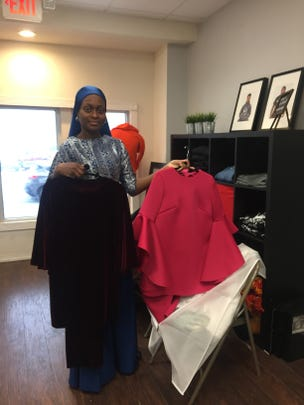 Nicole Muhammad shows two of her designs. She makes clothing for Muslim women and anyone who opts for a more modest but still vibrant look.