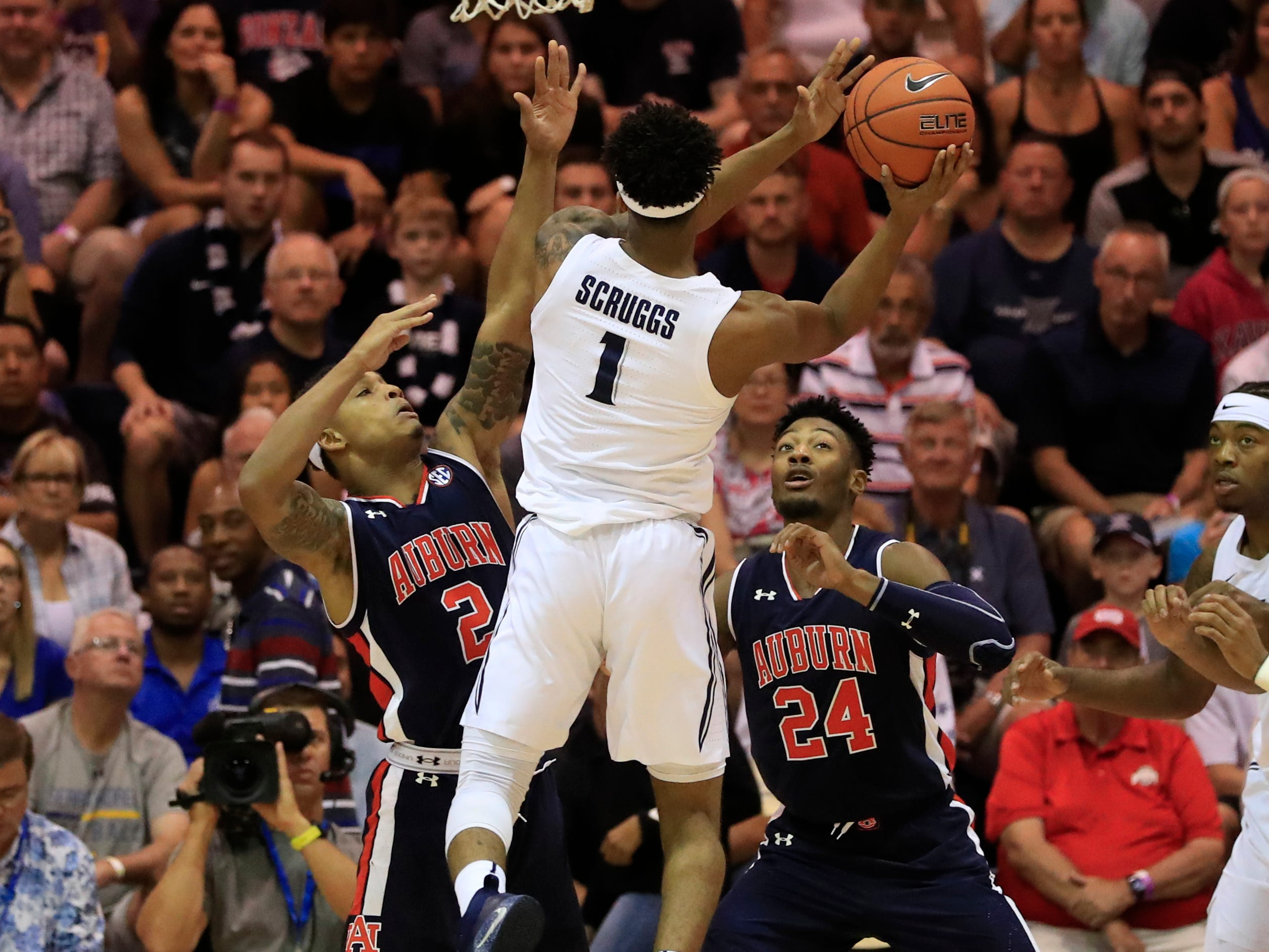 Auburn guard Bryce Brown (2) and forward Anfernee McLemore (24) try to guard Xavier guard Paul Scruggs (1) during the first half of an NCAA college basketball game at the Maui Invitational, Monday, Nov. 19, 2018, in Lahaina, Hawaii.