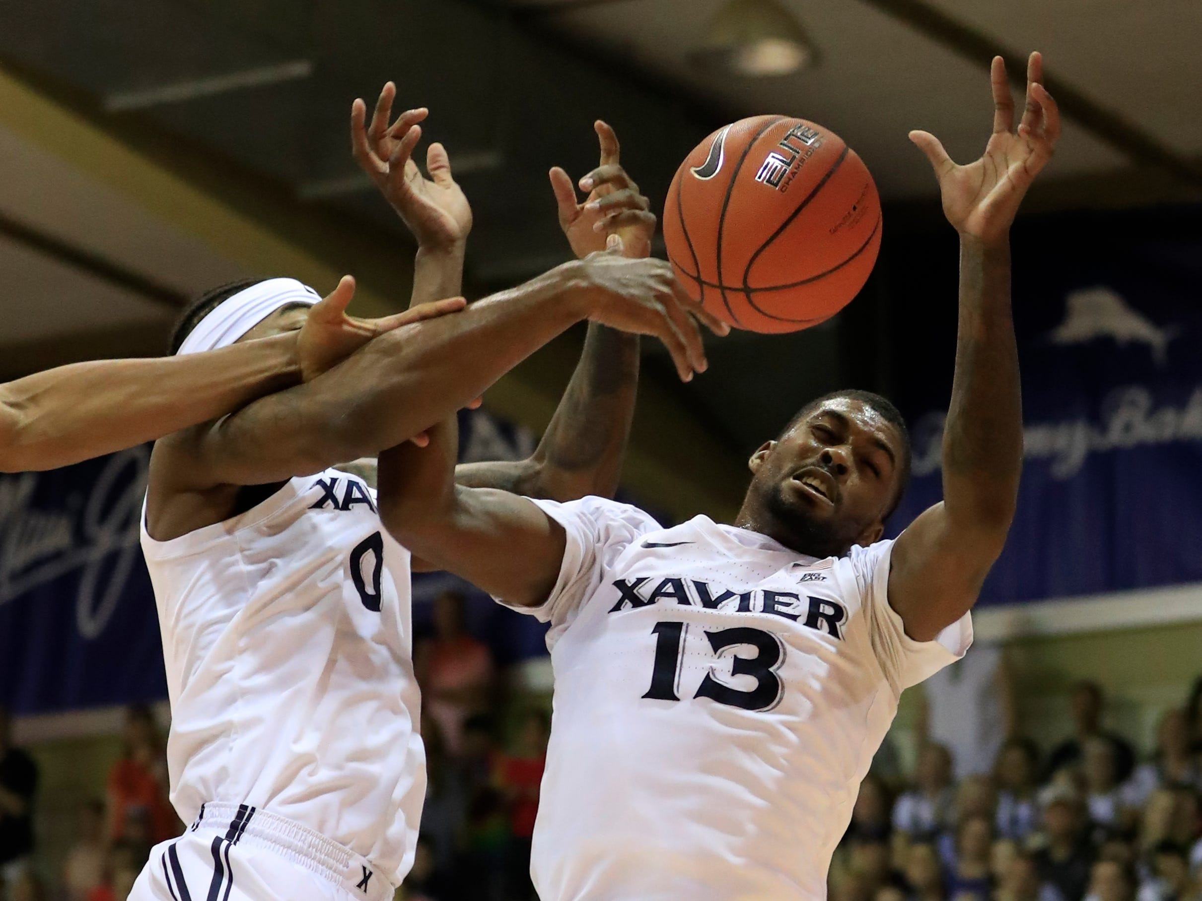Xavier forwards Tyrique Jones (0) and Naji Marshall (13) try to grab a rebound during the first half of an NCAA college basketball game against Auburn at the Maui Invitational, Monday, Nov. 19, 2018, in Lahaina, Hawaii.