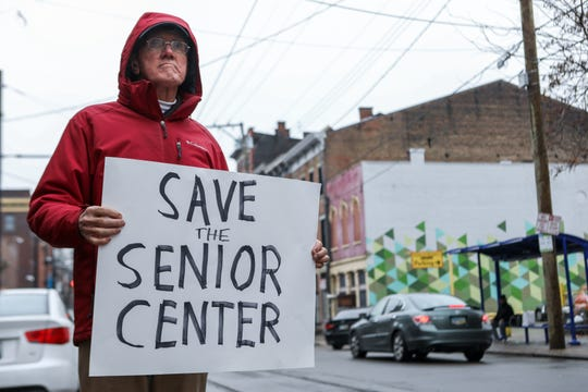Many rally outside of the OTR Senior Citizen Center in protest of its Nov. 28 closing. Thurman Wenzl stands away from the protest, instead holding up a sign by the street for cars passing by to notice.
