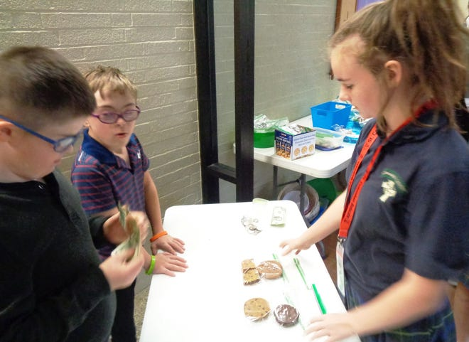 Loveland Intermediate School special needs students work alongside St. Columban students displaying their communication and counting skills at a benefit bake sale at the school.