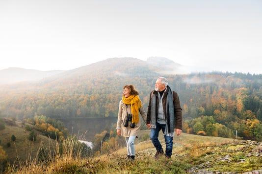 Senior Couple On A Walk In An Autumn Nature