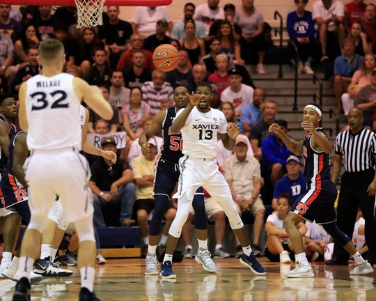 Xavier forward Naji Marshall (13) passes the ball to teammate Ryan Welage (32) during the first half of an NCAA college basketball game against Auburn at the Maui Invitational, Monday, Nov. 19, 2018, in Lahaina, Hawaii.