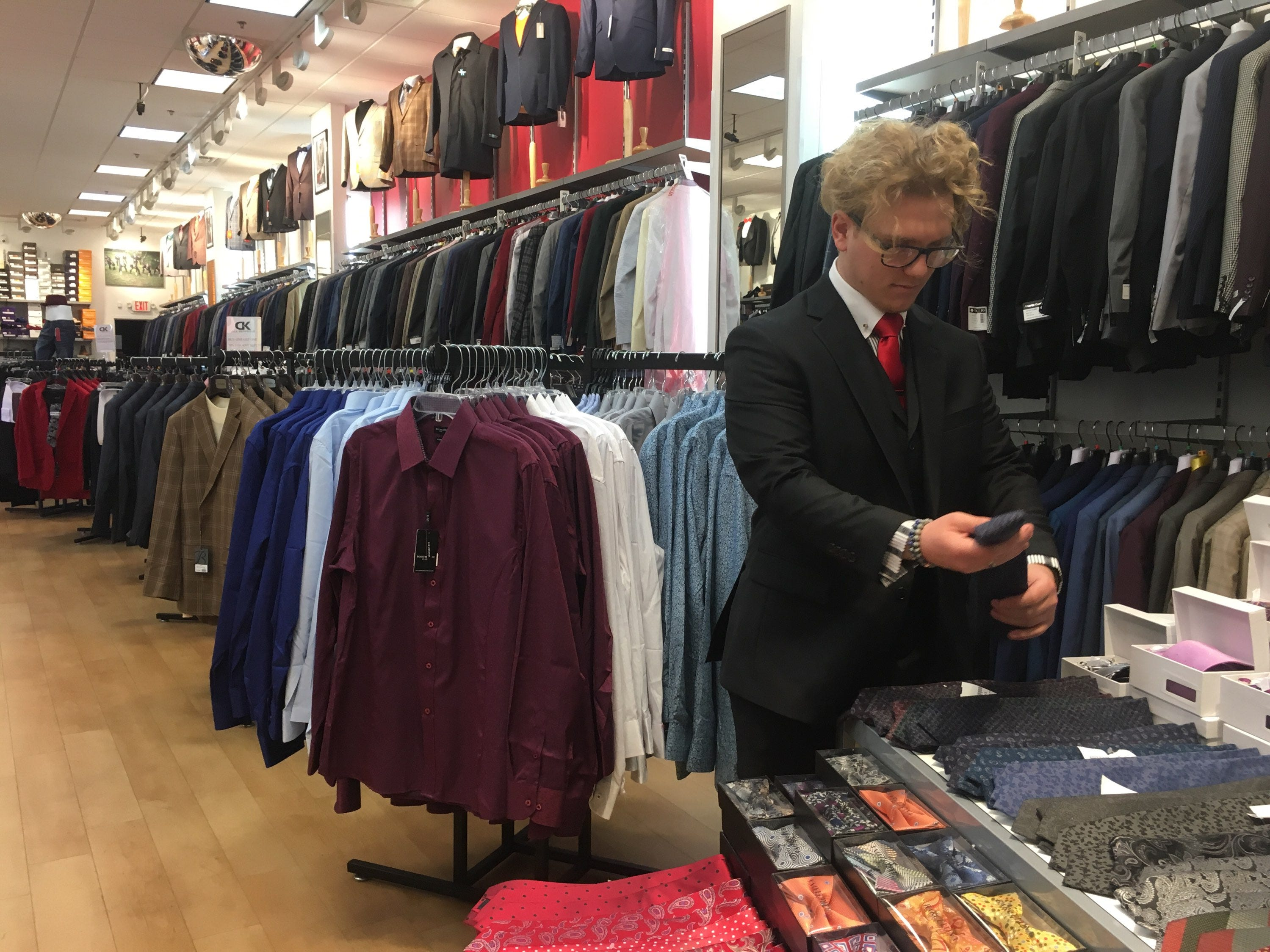 Austin Aderholt stocks men's neckties at D&K Menswear, a store that's entering its first Christmas shopping season in the Clarksville regional mall.