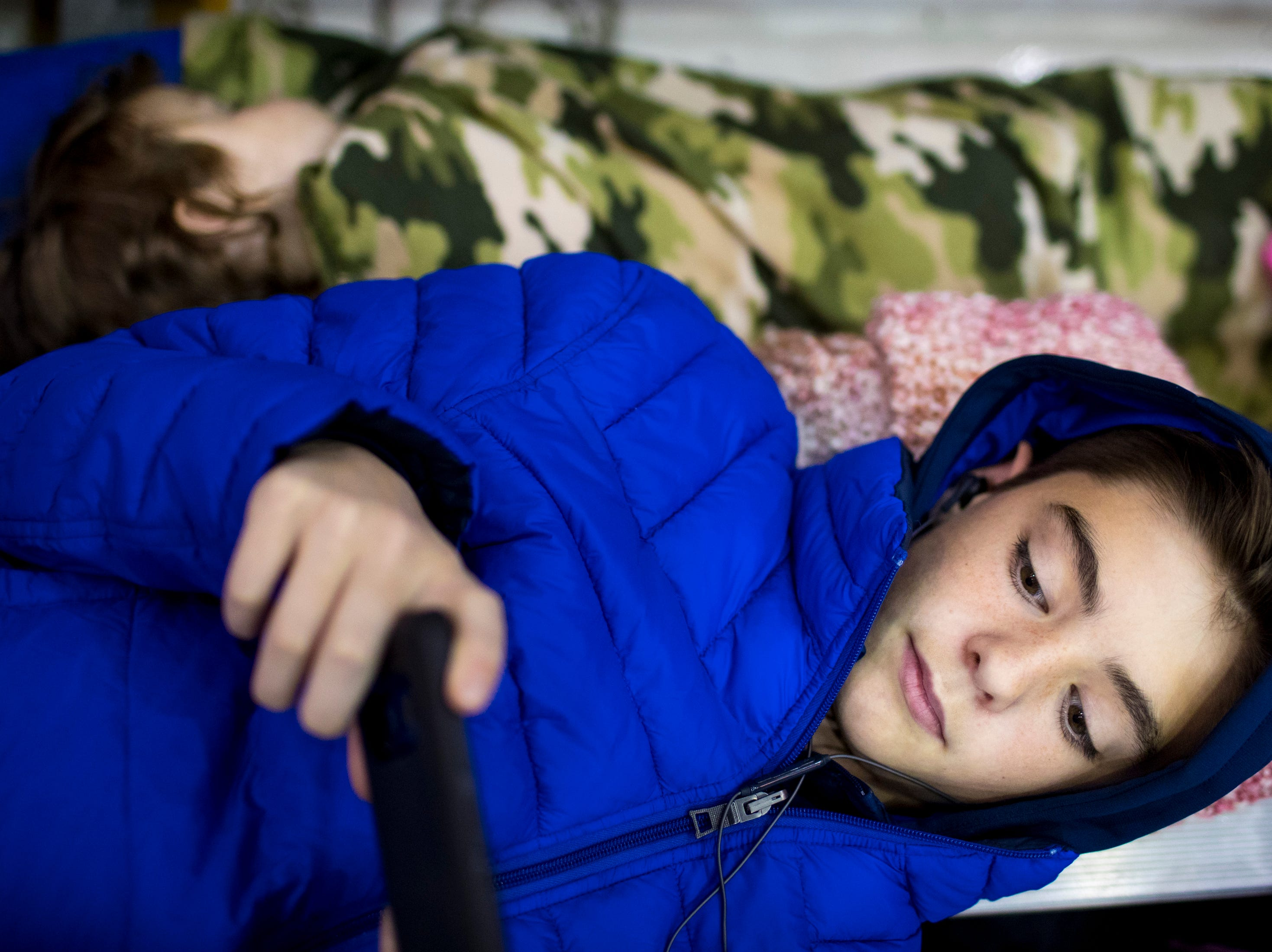 Ethan Miller, 13, watches Netflix on his phone as his sister Carmella Egner sleeps, while waiting for the plane carrying their father, 1st Lt. Justin Egner, to arrive during the welcome home ceremony for the 2nd Battalion, 44th Air Defense Artillery Regiment and 101st Airborne Division at Fort Campbell in the early hours of Monday, Nov. 19, 2018. The soldiers were returning from a 9-month deployment in Afghanistan.