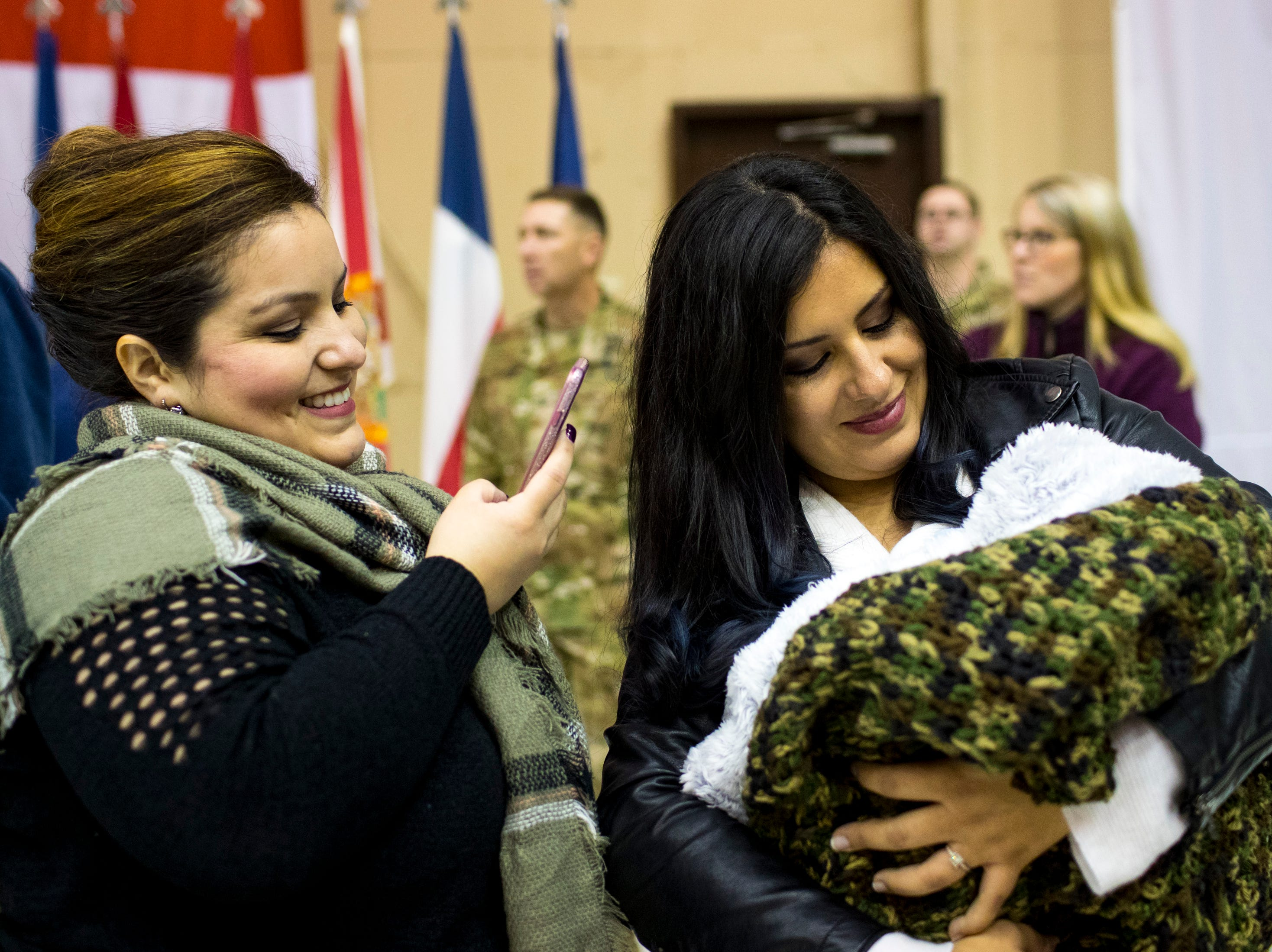 Annabel Rivera records her sister, Elizabeth Peterson, as she prepares to greet her husband, Sgt. Major Kevin Peterson, with their newborn son, Logan Grey Peterson, 1 week, during the welcome home ceremony for the 2nd Battalion, 44th Air Defense Artillery Regiment and 101st Airborne Division at Fort Campbell in the early hours of Monday, Nov. 19, 2018. The soldiers were returning from a 9-month deployment in Afghanistan.