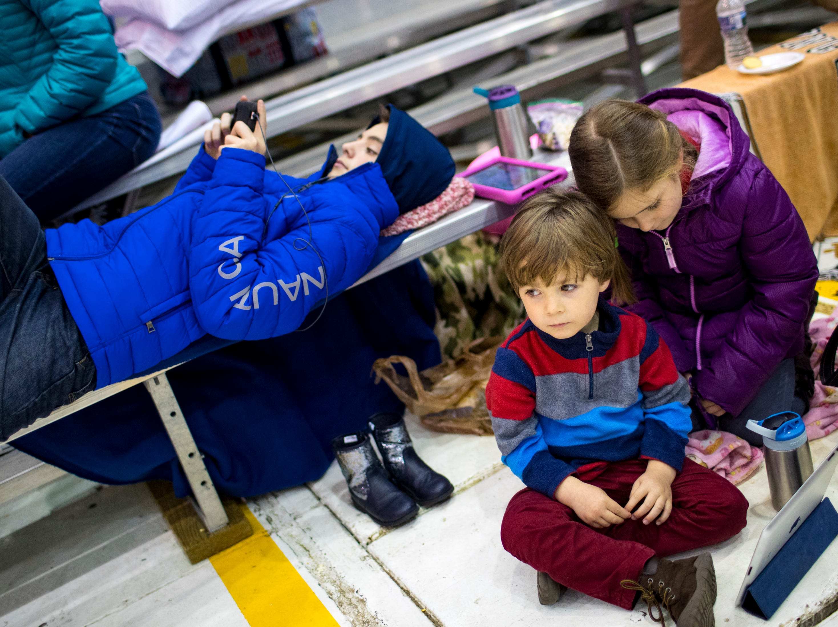Ethan Miller, 13, watches Netflix on his phone as Alexander Quandt, 3, and Valentina Quandt, 6, wait for the plane carrying their parents, 1st Lt. Justin Egner and 1st Lt. Daniel Quandt, to arrive during the welcome home ceremony for the 2nd Battalion, 44th Air Defense Artillery Regiment and 101st Airborne Division at Fort Campbell in the early hours of Monday, Nov. 19, 2018. The soldiers were returning from a 9-month deployment in Afghanistan.