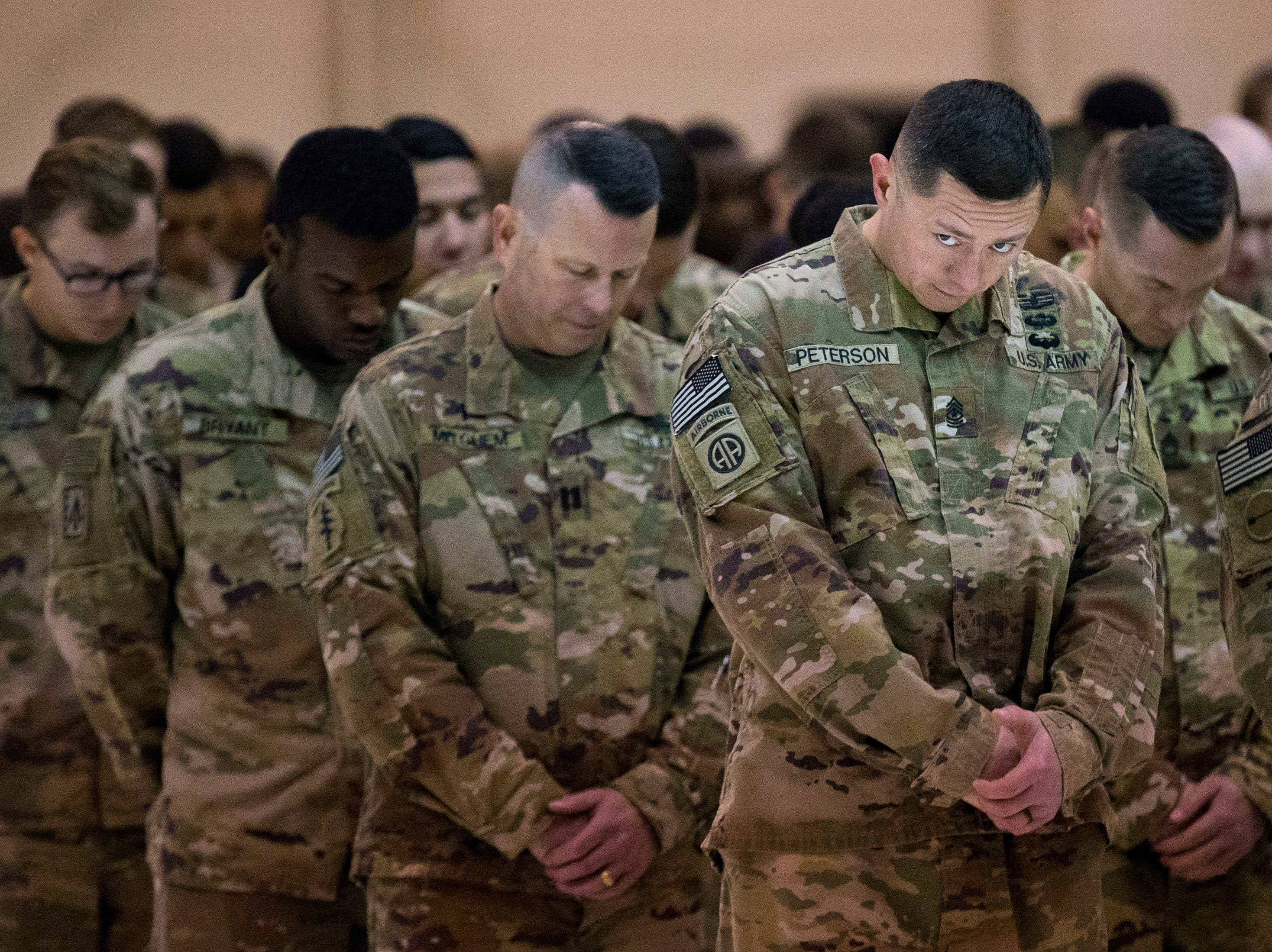 Sgt. Major Kevin Peterson glances up towards his wife and newborn son as a prayer is said during the welcome home ceremony for the 2nd Battalion, 44th Air Defense Artillery Regiment and 101st Airborne Division at Fort Campbell in the early hours of Monday, Nov. 19, 2018. The soldiers were returning from a 9-month deployment in Afghanistan.