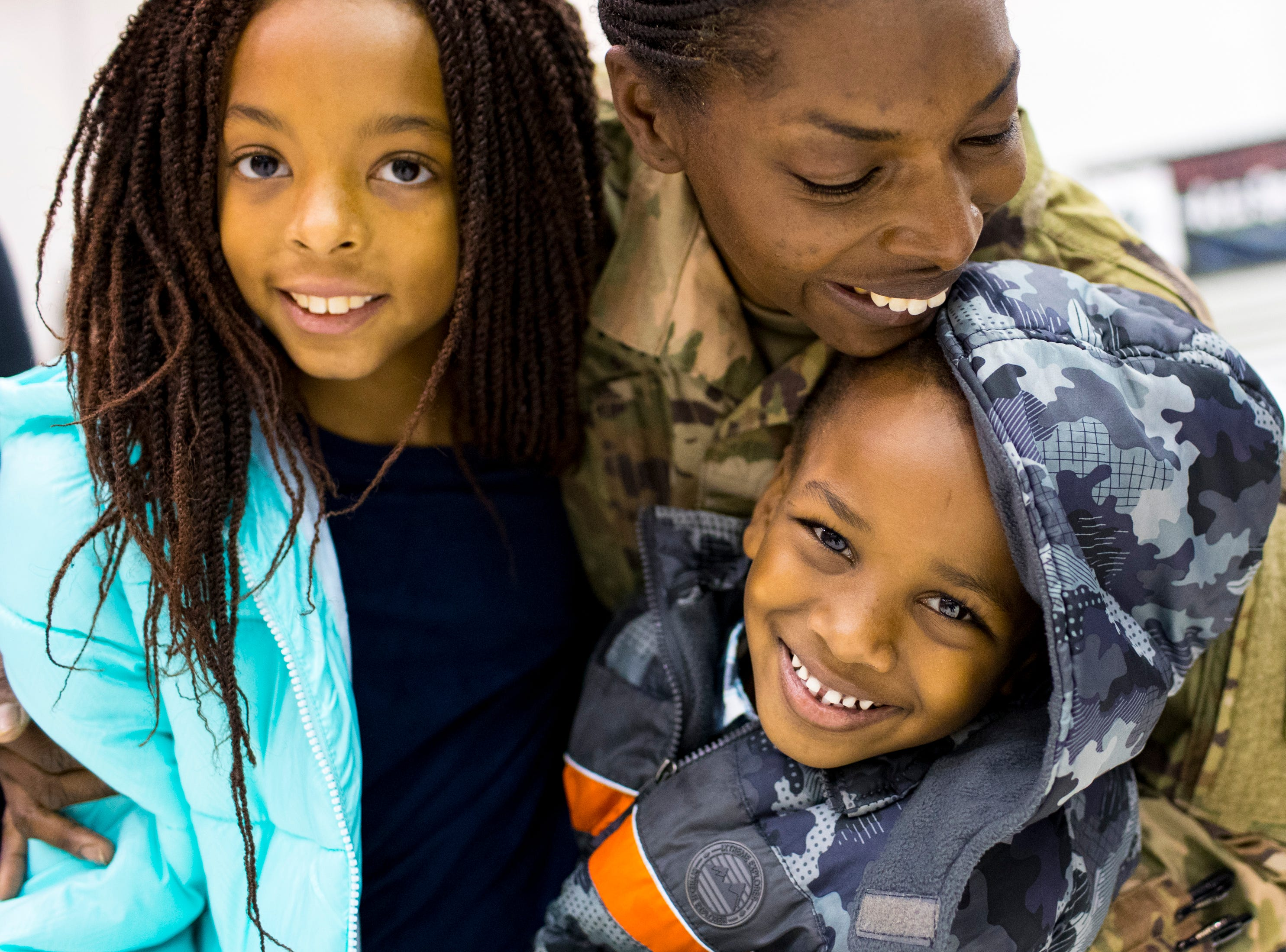 Staff Sgt. Felicia Witcher holds her children Mariana Hernandez, 8, and Justin Ewing, 5, during the welcome home ceremony for the 2nd Battalion, 44th Air Defense Artillery Regiment and 101st Airborne Division at Fort Campbell in the early hours of Monday, Nov. 19, 2018. The soldiers were returning from a 9-month deployment in Afghanistan.