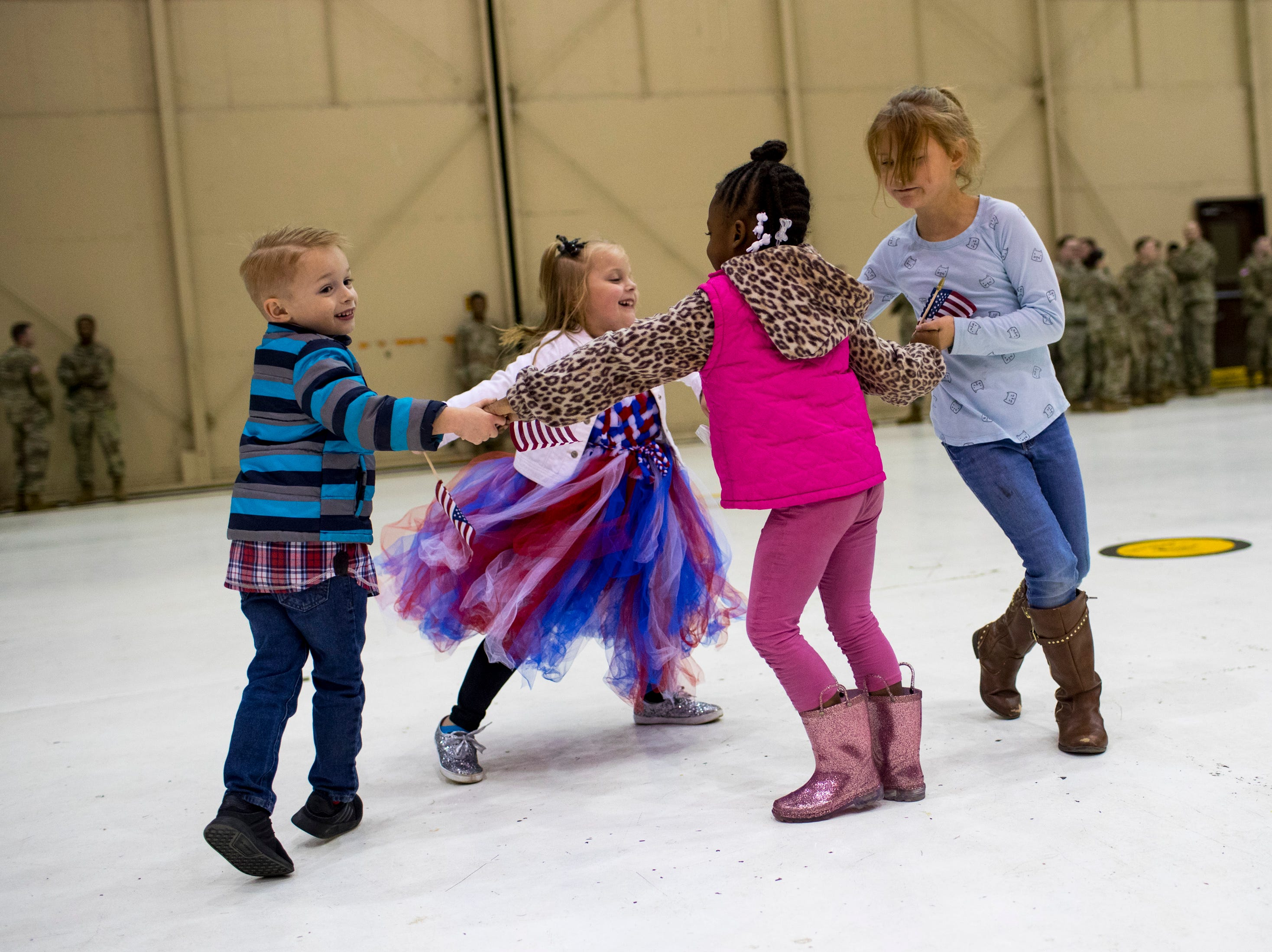 Ryan Purvis, 5, left to right, Khloe Purvis, 6, Faith Hill, 4, and Abigail Hawk, 9, dance while waiting for their family members to arrive during the welcome home ceremony for the 2nd Battalion, 44th Air Defense Artillery Regiment and 101st Airborne Division at Fort Campbell in the early hours of Monday, Nov. 19, 2018. The soldiers were returning from a 9-month deployment in Afghanistan.