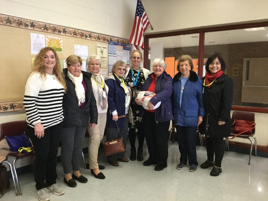 Members of the Bridgewater Woman's Club donate two dozen Thanksgiving turkeys and gift cards to Bridgewater-Raritan Middle School nurse Stephanie Hurley for area families.