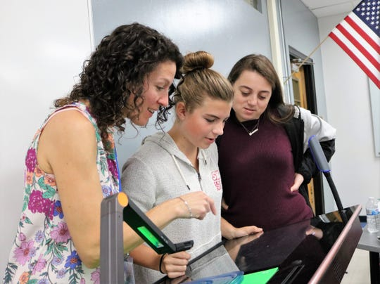 Left to right:  Engineering instructor Laura Doyle, sophomore Kathryn Evans, and senior Rebecca Wolfe use the hover camera feature on an interactive workstation in the new Innovation Classroom at Westfield High School.