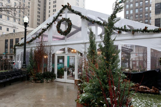 A holiday warming tent and seating area in Capitol Park next to pop-up shops on Sunday, Nov. 18, 2018 in Detroit.