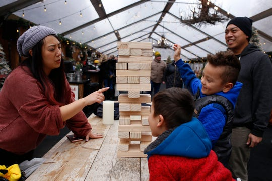 From left, Kelly Cho, of Detroit, decides which giant wooden block to pull from the game while her nephews, Austin Cho, 5, and Oliver Cho, 6, watch with her husband Rick Soliven from inside the Cadillac Lodge on Sunday, Nov. 18, 2018 in Cadillac Square in Detroit.