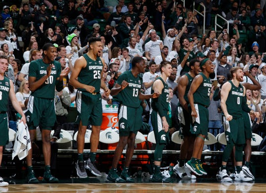 The Michigan State bench, including from left, Foster Loyer, Marcus Bingham Jr. Kenny Goins, Gabe Brown, Matt McQuaid, Xavier Tillman, Cassius Winston and Kyle Ahrens, celebrate in the closing moments of MSU's 101-33 win on Sunday, Nov. 18, 2018, in East Lansing.