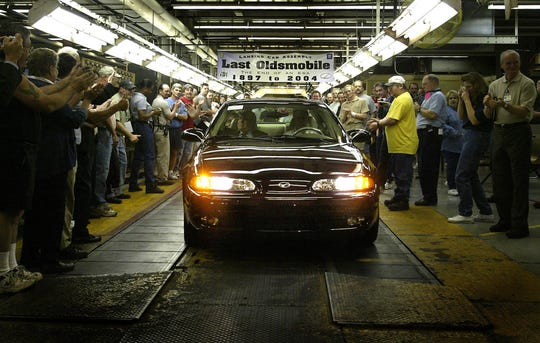 President of the Oldsmobile Dealer Council, George Nahas, in the passenger seat, rides along with GM employees,  Rick Parr, driving, Al Cooper and Bill Schleicher, back seat, in a 2004 Oldsmobile Alero GLS sedan as it leaves the assembly line n Lansing, Michigan on Wednesday, April 29, 2004. This vehicle is the last Oldsmobile to leave the assembly line at the Lansing Car Assembly Chassis Plant as the brand is being faded out. (GM Photo/Tom Pidgeon)