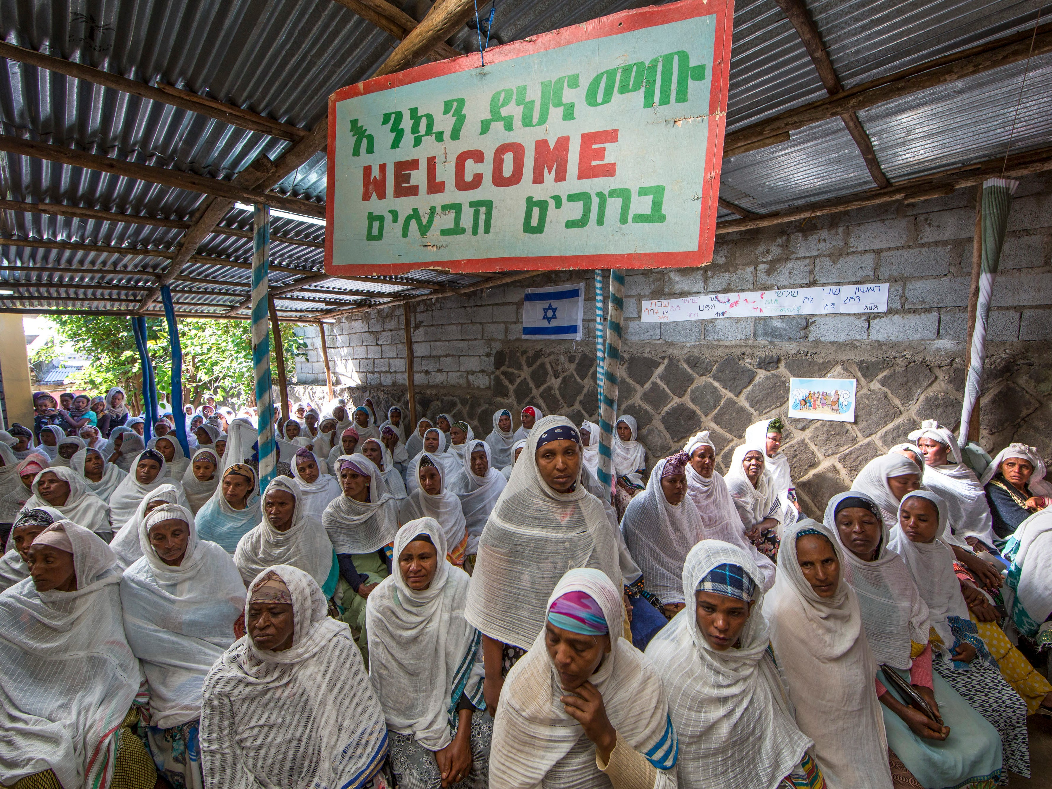 "Members of Ethiopia's Jewish community gather below a banner reading ""Welcome"" in Amharic, English and Hebrew, to protest the Israeli government's decision not to allow all of them to emigrate to Israel, leaving their families divided between the two countries, at the synagogue in Addis Ababa, Ethiopia Monday, Nov. 19, 2018. Representatives of the 8,000 Jews in Ethiopia urged the Ethiopian Jews living in Israel to think carefully before voting for Israel's ruling party, the Likud, over the delays in repatriation to Israel."