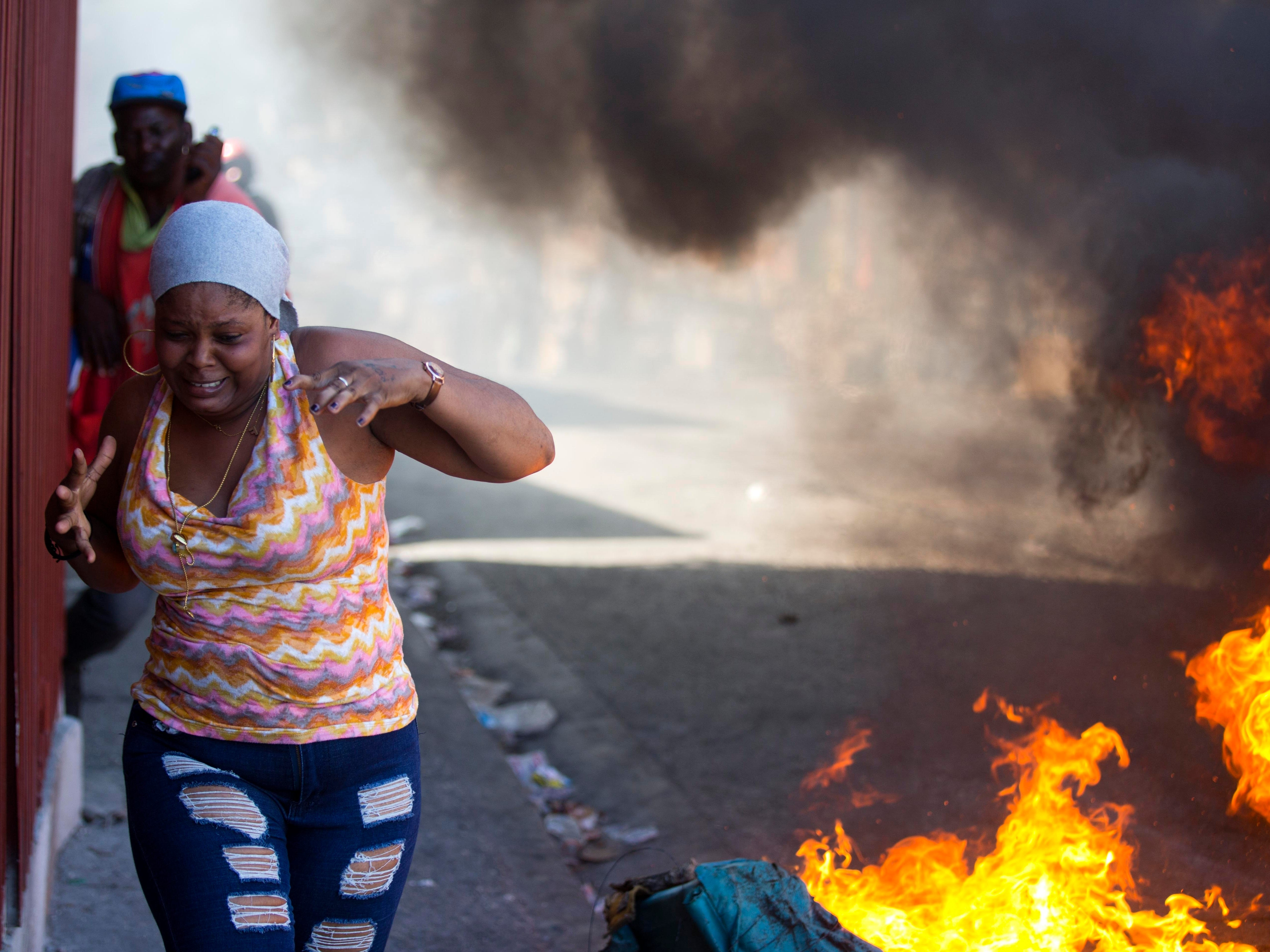 Residents run past burning barricades during a strike that is part of protests demanding to know how Petro Caribe funds have been used by the current and past administrations, in Port-au-Prince, Haiti, Monday, Nov. 19, 2018. Much of the financial support to help Haiti rebuild after the 2010 earthquake comes from Venezuela's Petro Caribe fund, a 2005 pact that gives suppliers below-market financing for oil and is under the control of the central government.