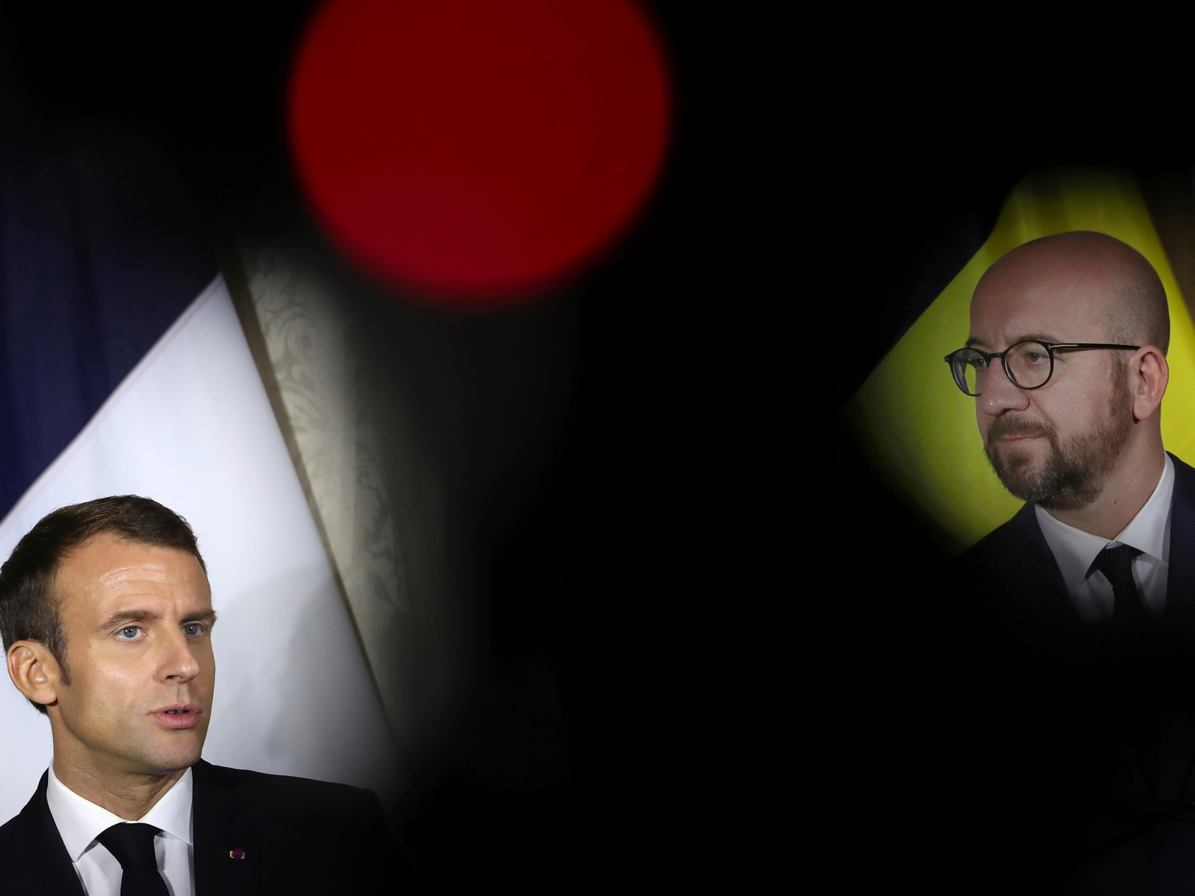 French President Emmanuel Macron, left, talks to journalists during a joint news conference with Belgian Prime Minister Charles Michel, right, following their meeting at the Egmont Palace in Brussels, Monday, Nov. 19, 2018. President Macron and the first lady are on a two day state visit to Belgium.