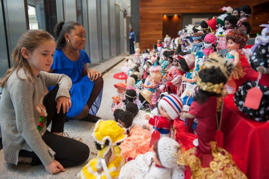 Judges Emily Stanczak, left, 9, of Auburn Hills and Amaria Clark, 10, of Redford Township carefully consider their choices from an array of fancifully dressed dolls during the annual judging of the Goodfellows doll-dressing competition at Comerica Bank in downtown Detroit on Monday.