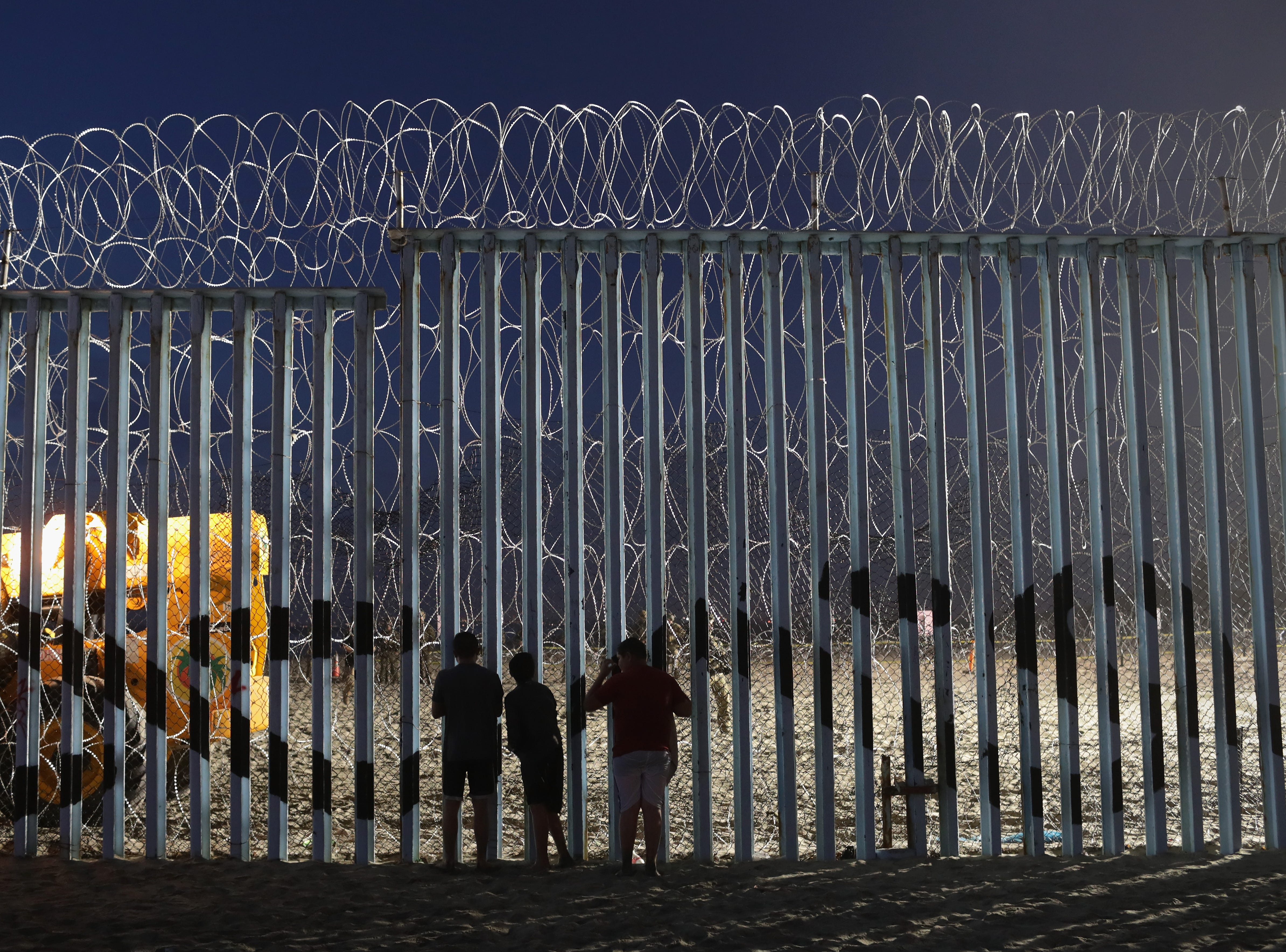 People look through the border fence on November 16, 2018 in Tijuana, Mexico. U.S. border agencies continued to fortify the fence with razor wire and additional personnel as members of the migrant caravan arrived to Tijuana across the border from San Diego.