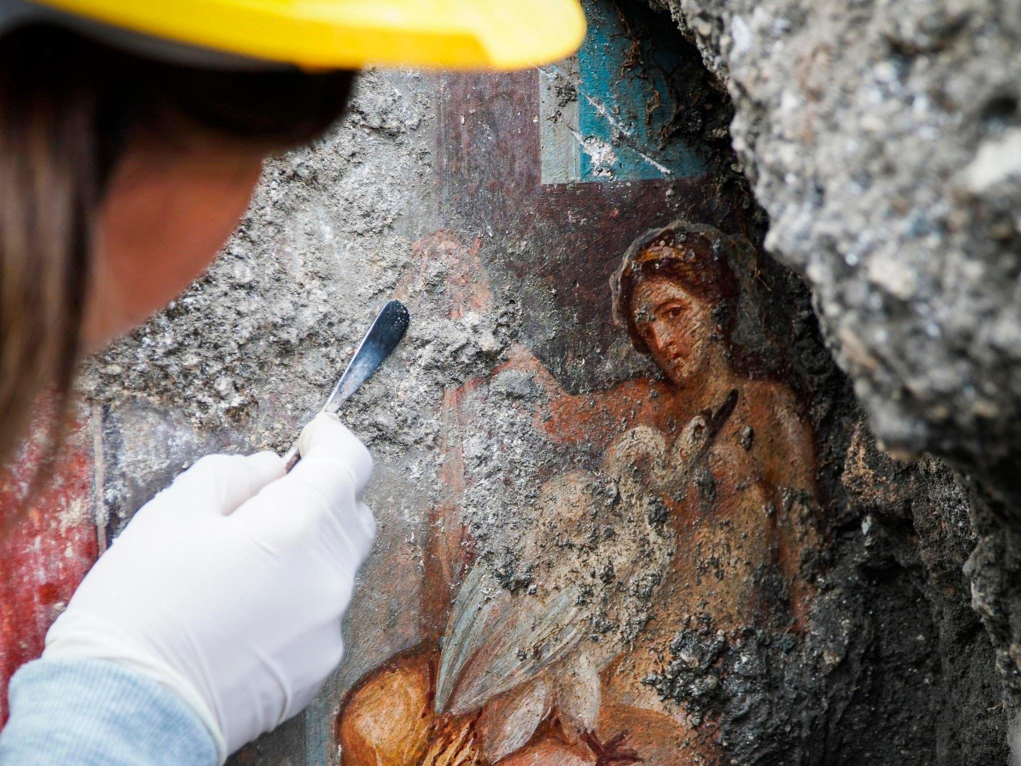 An archeologist cleans up the fresco ''Leda e il cigno'' (Leda and the swan) discovered last Friday in the Regio V archeological area in Pompeii, near Naples, Italy, Monday, Nov. 19, 2018. The fresco depicts a story and art subject of Greek mythology, with goddess Leda being impregnated by Zeus -  Jupiter in Roman mythology - in the form of a swan.